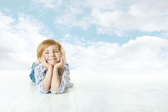 Smiling child lying down, small kid blue sky royalty free stock photos
