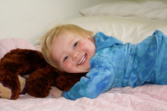 Smiling child lying on stuffed animal. Closeup of laughing blond child lying on stuffed animal wearing vibrant blue clothing Stock Image