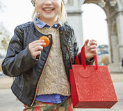 Smiling child near Arc de Triomphe holding French macaroon. Stylish autumn in Paris. Closeup on smiling elegant child with red present bag near Arc de Triomphe Stock Photography