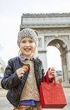 Smiling child near Arc de Triomphe holding French macaroon. Stylish autumn in Paris. Portrait of smiling elegant child with red present bag near Arc de Triomphe Stock Images