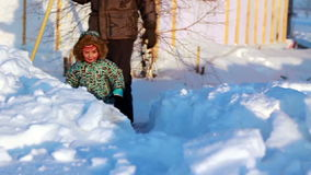 Smiling child is on the newly cleared path in snow stock footage