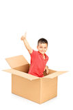 Smiling child in a paper box giving thumb up and looking at came Royalty Free Stock Images