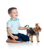 Smiling child playing with a puppy dog Stock Images