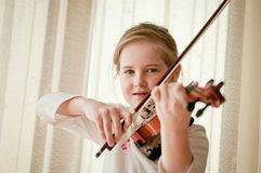 Smiling child playing violin at home Royalty Free Stock Photos