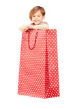 A smiling child posing in a red spotted shopping bag Royalty Free Stock Photography