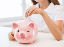 Smiling child putting coin into big piggy bank Royalty Free Stock Photography