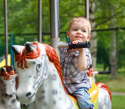 Smiling child riding a toy horse carousel Royalty Free Stock Photography