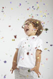 Smiling child with rimmed glasses and confetti Royalty Free Stock Photos