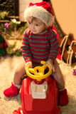 Smiling child in Santa hat is sitting in a baby car Stock Photography