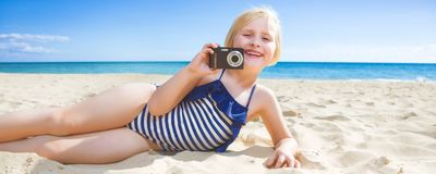 Smiling child on seacoast taking photo with digital camera. Sun kissed beauty. smiling healthy child in beachwear on the seacoast with digital camera taking stock photo