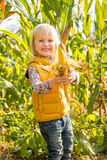 Smiling child showing corn while in cornfield Royalty Free Stock Images