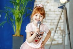 Smiling child sings a song into the microphone. The concept is c. Hildhood, lifestyle, music, singing, listening, hobbies royalty free stock image