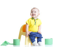 Smiling child sitting on chamber pot with toilet. Paper rolls royalty free stock photo