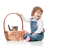 Smiling child sitting down by basket with kittens Stock Images