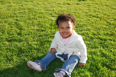 Smiling child sitting in grass Stock Images