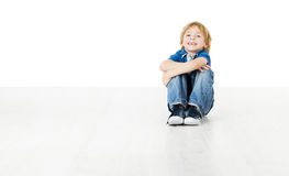 Smiling child sitting on white floor Stock Photo