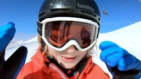 Smiling child skiing and waving hand on snow mountain