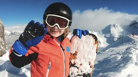 Smiling child with snowboard on snow mountain background