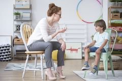 Smiling child and speech therapist. Smiling child on a mint chair talking to a speech therapist at school stock images