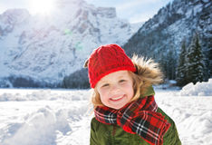 Smiling child standing in the front of snowy mountains Stock Photography