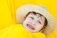 A smiling child in a straw hat lies nestled in yellow towel Royalty Free Stock Photos
