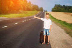Smiling child with suitcase traveling hitchhiking. summer road Royalty Free Stock Photography