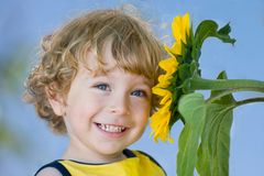 Smiling child with sunflower Royalty Free Stock Photo