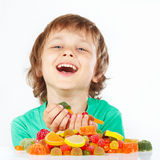 Smiling child with sweets and candies on white background royalty free stock photography