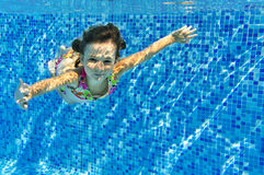 Smiling child swims underwater in pool Stock Photography