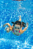 Smiling child swims underwater in pool Royalty Free Stock Photo