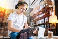 Smiling child using his new tablet and looking glad. Wonderful device. Progressive smiling boy sitting on the table and feeling happy while listening to music in Royalty Free Stock Images