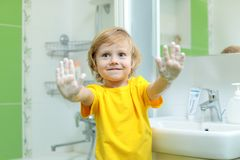Smiling child washing hands and showing soapy palms royalty free stock photography