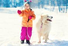 Smiling child and white Samoyed dog on leash walking winter Royalty Free Stock Photos