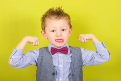 Smiling child who shows muscles. A smiling child who shows muscles Stock Photo
