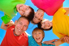 Smiling children. Wearing bright colored shirts standing in a circle against a blue sky stock photography
