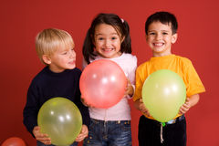 Smiling children with ballons. In red background Royalty Free Stock Photography