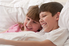 Smiling children in bed playing. Close-up. Stock Photography