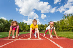 Smiling children on bending knees ready to run. Smiling children on bending knees in ready position to run marathon in summer royalty free stock photography