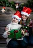 Smiling children with Christmas gift and New Year tree. Making present. Stock Photo