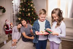 Smiling children with christmas gifts. Selective focus of smiling children with christmas gifts with parents behind at home royalty free stock photos