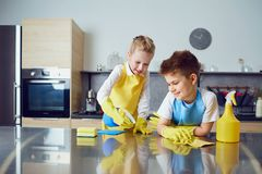 Smiling children do the cleaning in the kitchen.  royalty free stock images