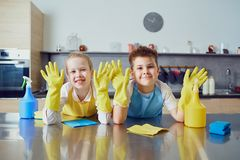 Smiling children do the cleaning in the kitchen.  stock photo