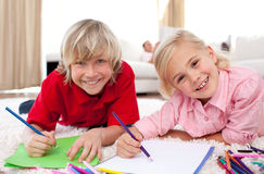 Smiling children drawing lying on the floor Stock Image