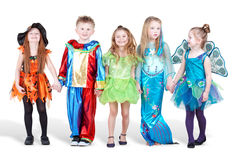 Smiling children dressed in carnival suits stand