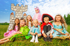 Smiling children in festival costumes sit close Royalty Free Stock Images