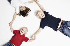 Smiling children on floor holding hands Royalty Free Stock Photos
