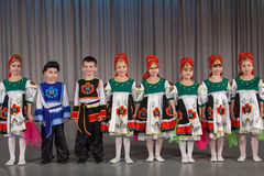 The smiling children in folk costume performs on stage Stock Photo