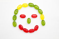 Smiling children girl face made of candy. Heap colors candy in glass bowl on white Royalty Free Stock Images