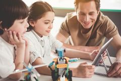 Positive kids using digital device. Smiling children and glad men looking at electronic tablet. They using it to make order for robot. Technology of future Royalty Free Stock Image