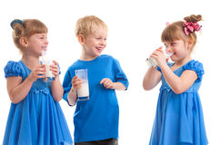 Smiling children with a glass of milk. Little girls-twins and boy are drinking milk of glasses in their hands and are laughing on white background Stock Photos